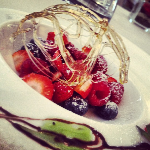 Fruit salad with strawberries, blackberries and raspberries in a nest of caramel